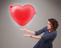 Giovane signora che tiene il cuore adorabile di rosso 3d Immagine Stock