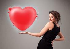 Giovane signora che tiene il cuore adorabile di rosso 3d Immagine Stock Libera da Diritti