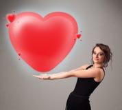 Giovane signora che tiene il cuore adorabile di rosso 3d Immagini Stock
