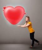 Giovane signora che tiene il cuore adorabile di rosso 3d Fotografie Stock Libere da Diritti