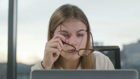 Giovane signora con i vetri che esaminano il computer portatile video d archivio