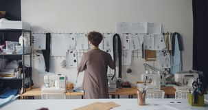 Giovane signora del sarto che tocca i disegni sulla parete che progetta la nuova raccolta dei vestiti stock footage