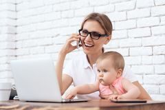 Giovane signora di affari prova a lavorare con poco bambino fotografia stock libera da diritti