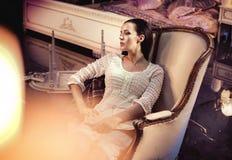 Giovane signora di Beautfiul che riposa in una poltrona lussuosa e antica immagini stock libere da diritti