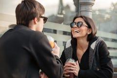 Giovane signora di risata che si siede all'aperto con suo fratello Immagini Stock