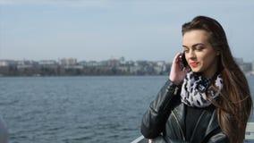 Giovane signora felice che comunica sul telefono mobile video d archivio