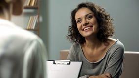 Giovane signora felice che parla con lo psicologo alla clinica, sessione della terapia di riabilitazione fotografia stock libera da diritti