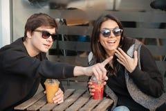 Giovane signora felice che si siede all'aperto con il suo succo bevente del fratello Immagini Stock Libere da Diritti