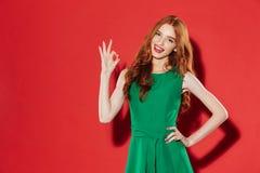 Giovane signora felice della testarossa in vestito verde che mostra gesto giusto Fotografia Stock Libera da Diritti