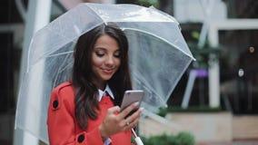 Giovane signora felice di affari che sta sulla via urbana e che utilizza smartphone che dura nel cappotto rosso Lei che tiene omb video d archivio