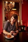 Giovane signora graziosa che manda un sms alla tavola Immagini Stock Libere da Diritti