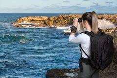 Giovane signora graziosa con il binocolo alla costa Fotografia Stock