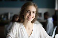 Giovane signora graziosa sorridente che esamina macchina fotografica nel luogo pubblico Immagine Stock