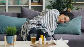 Giovane signora malata che fa un sonnellino sullo strato a casa nell'ambito del rilassamento generale caldo archivi video