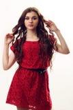 Giovane signora nel dancing rosso del vestito sul fondo bianco Fotografia Stock