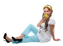 Giovane signora nella seduta sul pavimento e nel cibo della mela Immagine Stock