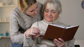 Giovane signora preoccupantesi che dà gli occhiali al libro di lettura invecchiato della nonna in sedia a rotelle video d archivio