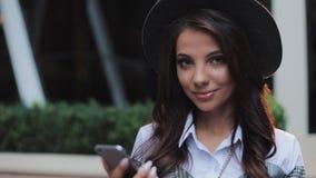 Giovane signora professionale di affari che sta sulla via urbana e che per mezzo dello smartphone Lei che esamina la macchina fot archivi video