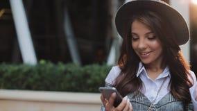 Giovane signora professionale di affari che sta sulla via urbana e che per mezzo dello smartphone Lle buone notizie leggenti dell stock footage