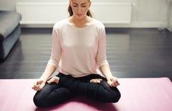Giovane signora rilassata che medita a casa Fotografia Stock Libera da Diritti
