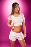 Giovane signora sexy nella posa bianca con i piccoli bilancieri Fotografia Stock