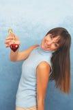 Giovane signora sorridente in blu-chiaro con una decorazione rossa del cuore Giorno del biglietto di S Fotografia Stock Libera da Diritti