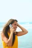Giovane signora sorridente che comunica su un cellulare Fotografie Stock Libere da Diritti