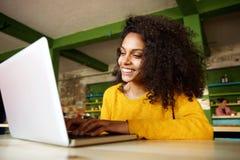 Giovane signora sorridente che lavora al computer portatile al caffè Fotografia Stock Libera da Diritti