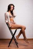 Giovane signora sorridente che si siede su una sedia Immagini Stock
