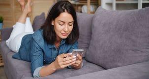 Giovane signora sorridente facendo uso dello schermo di contatto dell'aggeggio della tenuta dello smartphone a casa archivi video