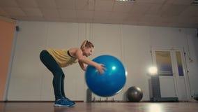 Giovane signora sportiva sta esercitandosi da solo con Fitball alle mani nella palestra di addestramento archivi video