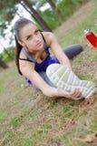 Giovane signora su erba che allunga in avanti sopra la gamba Immagini Stock Libere da Diritti