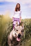 Giovane signora su una passeggiata con un cane Immagine Stock