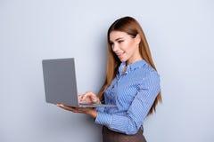 Giovane signora sveglia di affari sta tenendo il computer portatile e sta scrivendo su  lei immagini stock