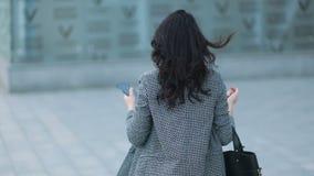 Giovane signora tenera di affari in rivestimento rigoroso con capelli marrone scuro che cammina sulla via urbana con lo smartphon stock footage