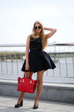 Giovane signora in vestito da cocktail e scarpe a tacco alto che posano outdoo fotografie stock