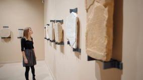 Giovane signora Visits il museo e gli sguardi alle pietre antiche con le iscrizioni stock footage