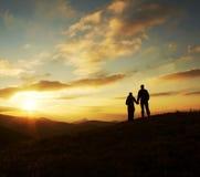 Giovane siluetta della famiglia per il tramonto fotografia stock