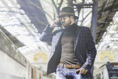 Giovane Smart Phone ispanico sicuro attraente della tenuta dell'uomo d'affari nella sua mano e nella chiamata mentre lui che sta  immagini stock libere da diritti