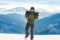 Giovane snowboard della tenuta dello snowboarder sui suoi sholders e sulla camminata alla cima stessa di una montagna Fotografie Stock