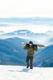 Giovane snowboard della tenuta dello snowboarder sui suoi sholders e sulla camminata alla cima stessa di una montagna nevosa Fotografie Stock