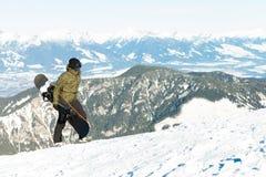 Giovane snowboarder che giudica il suo bordo disponibile e che scala alla cima di una montagna Fotografia Stock