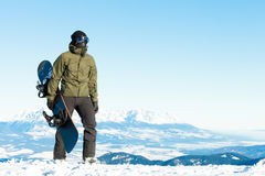 Giovane snowboarder che giudica il suo snowboard disponibile e che fa una passeggiata alla cima di una montagna Fotografie Stock