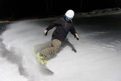 Giovane snowboarder che guida giù il pendio di montagna alla notte fotografia stock libera da diritti