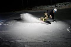 Giovane snowboarder che guida giù il pendio di montagna nevoso alla notte immagini stock
