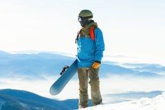Giovane snowboarder che sta alla cima stessa di una montagna e che tiene il suo snowboard con una mano Immagine Stock Libera da Diritti