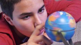 Giovane sogno teenager girando un globo della terra video d archivio