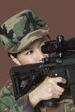 Giovane soldato degli Stati Uniti Marine Corps della femmina che tende fucile di assalto M4 sopra fondo marrone Immagini Stock Libere da Diritti