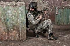 Giovane soldato dietro l'ostacolo immagine stock