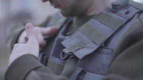 Giovane soldato irriconoscibile che mette sulla sua fine leggera del giubbotto antiproiettile su L'uomo che prepara per la guerra archivi video